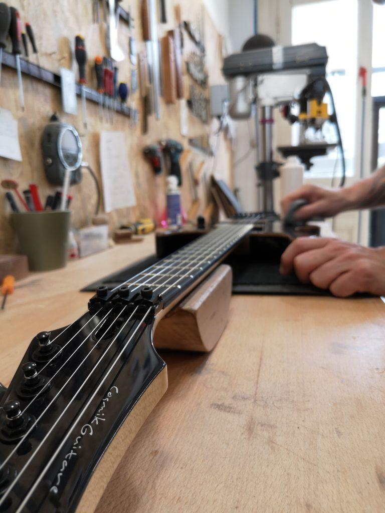 Frank Bolaers en train de travailler sur une guitare dans son atelier Cosmik Guitare