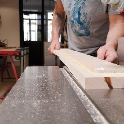 Frank taillant du bois dans son atelier pour la fabrication d'une guitare